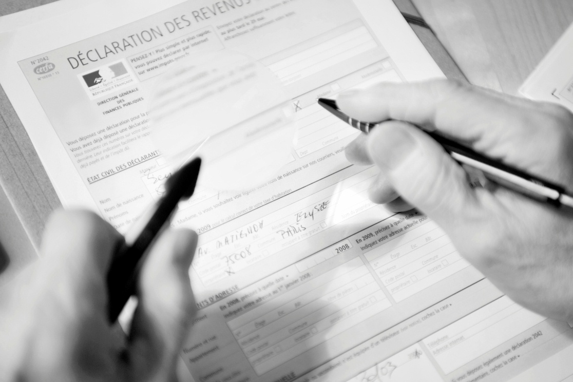 Close-up of a man's hands filling a form